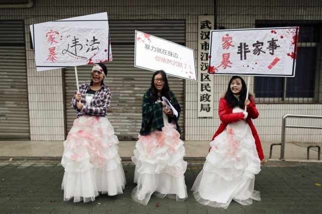 Chinese University students dressed as battered wives hold banners in front of an office of China's Civil Affairs department, where local people register for marriage, in protest of domestic violence.